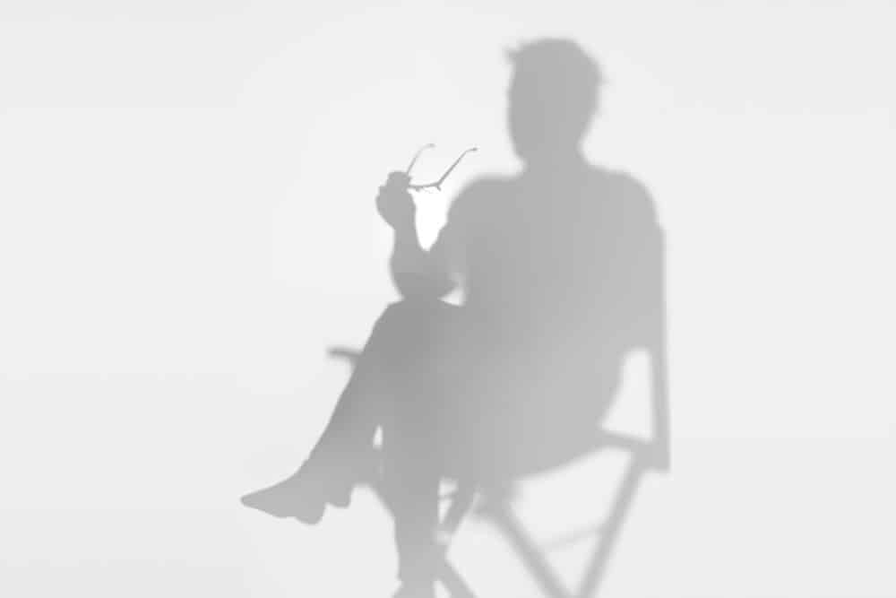 Shadow director sitting on deckchair and holding reading glasses
